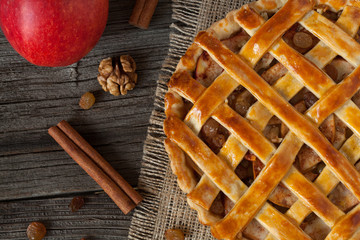 Apple pie with cinnamon on retro wooden background. Top view