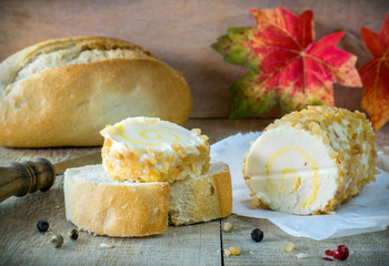 A roll of soft cheese and bread on rustic board