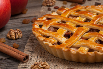 Apple pie with raisins and cinnamon on vintage wooden background