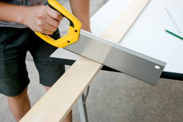 Carpenter working on a hand saw cutting wood board