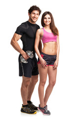 Athletic couple - man and woman with dumbbells on the white