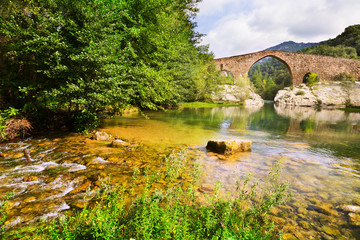 Mountain river with medieval arched bridge in  Pyrenees