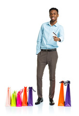 Happy african american man with shopping bags and holding credit