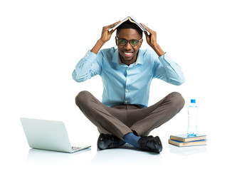 Happy african american college student with laptop, books and bo