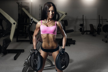 Young sexy fitness brunette woman in the gym doing exercises