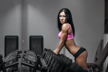 Brunette fitness woman in black sport wear with perfect body
