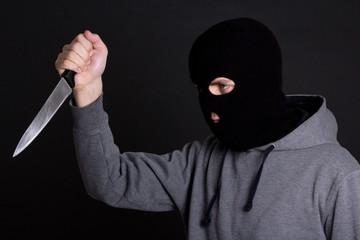 man criminal in black mask with knife over grey