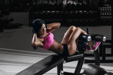 fitness woman in in gym performing sit up on bench