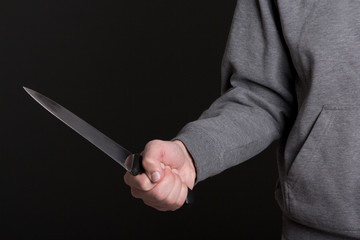 close up of knife in male hand over grey