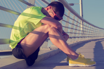Tired/injured jogger on a big bridge.