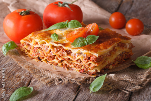 Leinwandbild Motiv Italian lasagna with basil close-up on paper, horizontal rustic