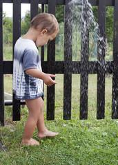 Child under garden water shower