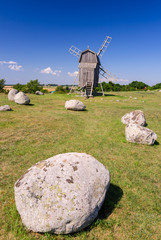 Ancient stone henge in front of traditional windmill