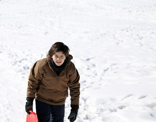 young boy walks with tobogganing  on fresh snow in the winter