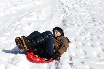 boy plays with sledding on snow