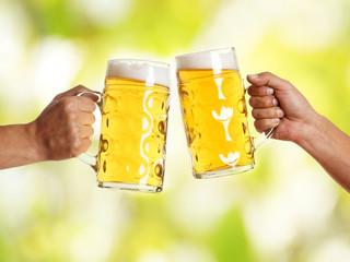 zwei Männerhände mit Bierkrug stoßen an vor grünen Hintergrund