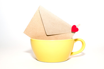 Envelope with heart is in the yellow cup on a white background.