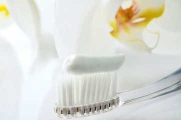 toothbrush with toothpaste on a white table against the backgrou