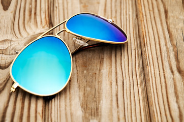 blue mirrored sunglasses on the wooden background close up