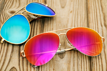 two colored sunglasses on the wooden background