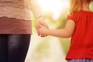 Mutter und Tochter gehen spazieren Hand in Hand