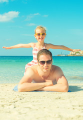 Man and little girl on the beach vacation.