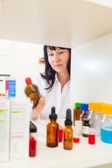 woman takes a bottle of medicine from the pharmacy