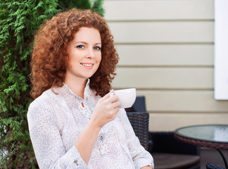 Pretty young woman sitting in a cafe with a cup of coffee