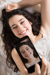 Happy young woman making a selfie in bed