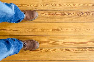 Füße und Schuhe auf Holzdielen