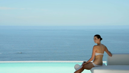 Woman relaxing by the pool