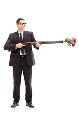 Businessman holding a rifle loaded with flowers