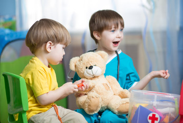 children play doctor with plush toy