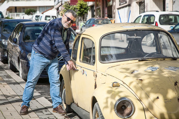 Man with an old classic yellow wolsvagen beetle