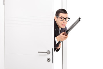 Terrified man with rifle entering a room