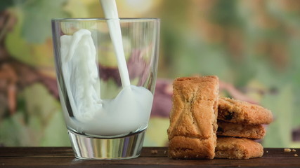 Pouring glass of milk and cookies