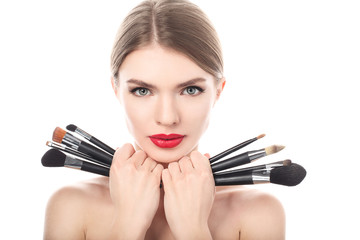 Portrait of beautiful woman with make-up brushes near face