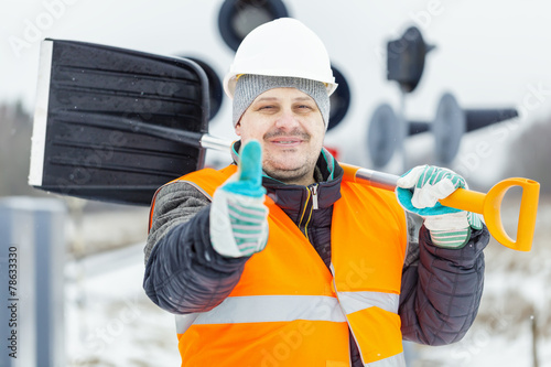 Worker with snow shovel near signal beacons in snowy day - 78633330