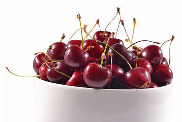 Red cherries in a white bowl on a white