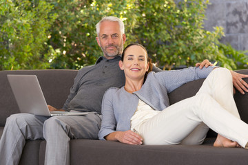 Couple surfing the web on sofa