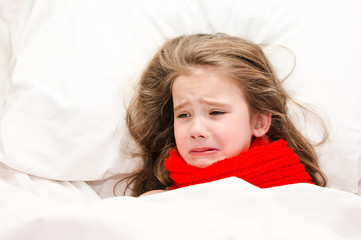 Sick little girl lying in the bed in red scarf