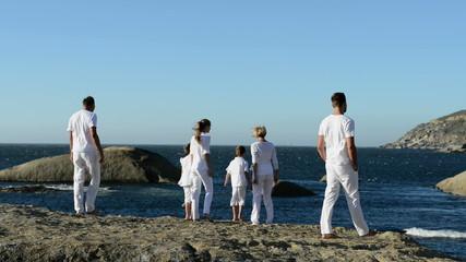 Multi generation family walking on beach rocks