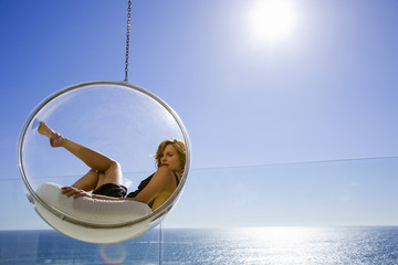 Woman in a bubble hanging chair