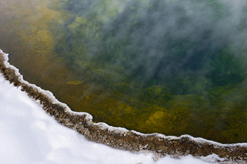 Colorful geyser basin in winter