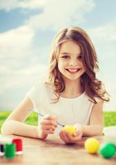 smiling little girl coloring eggs for easter