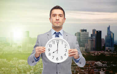 businessman in suit holding clock with 8 o'clock