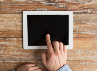 close up of male hands with tablet pc on table