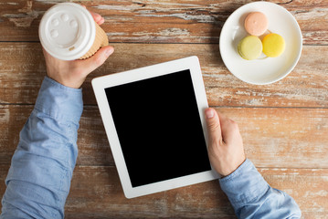 close up of male hands with tablet pc and coffee