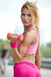 female fitness instructor exercising with small weights in city