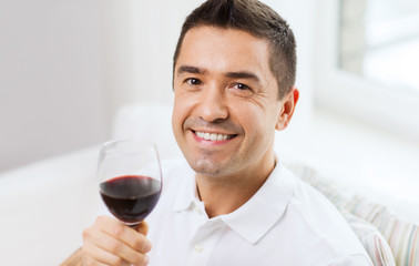 happy man drinking red wine from glass at home